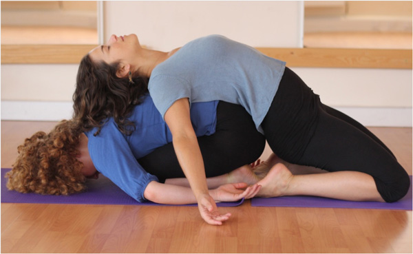Two women in yoga pose together